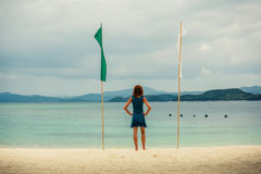 Woman on tropical beach with flags Stock Image