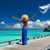Woman on a beach jetty at Maldives. Woman on a tropical beach jetty at Maldives Stock Image