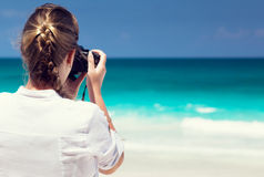 Woman on tropical beach taking photo Royalty Free Stock Image