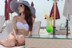 Woman with Tropical Drink Relaxing at Beach Resort Royalty Free Stock Photography