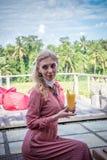 Woman with tropical mango juice outdoors, cafe. Bali island. Royalty Free Stock Photos