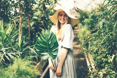 Woman in tropical orangery with monstera leaf royalty free stock images