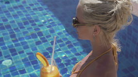 Woman at tropical resort hotel. Sensual blond woman wearing crochet bikini and sunglasses smiling, drinking orange juice and enjoying summer day while sitting at stock video