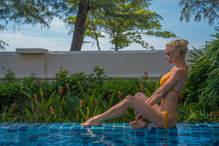 Woman at tropical resort hotel. Side view of sensual blond woman wearing crochet bikini relaxing at the edge of swimming pool at tropical resort hotel over sky royalty free stock photos