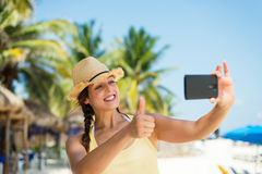 Woman on tropical summer vacation taking selfie with smartphone Stock Images