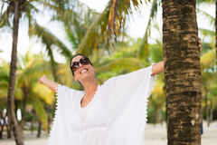 Woman on tropical vacation joy and fun. Stylish fashionable woman enjoying and having fun on summer tropical vacation at beach. Female brunette wearing fashion Stock Photos
