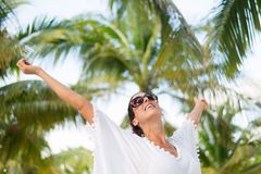 Woman on tropical vacation joy and fun. Stylish fashionable woman having fun and enjoying relaxing summer tropical vacation at beach. Female brunette wearing Royalty Free Stock Image