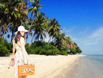 Woman on tropical vacation. Young woman with retro suitcase and shoes in hand on tropical vacation Royalty Free Stock Photo