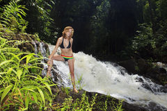 Woman by a tropical waterfall Royalty Free Stock Photo