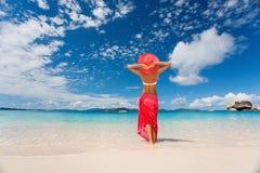 Woman tropics. Beautiful woman in red sarong on tropical beach Stock Image