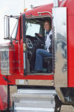 Woman truck driver. A pretty woman ready to drive a semi-truck with a loaded trailer behind it Royalty Free Stock Photos