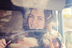Woman truck driver in the car. Girl smiling at camera and holding the steering wheel. Royalty Free Stock Photography