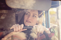 Woman truck driver in the car. Girl smiling at camera and holding the steering wheel. Royalty Free Stock Images