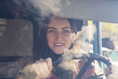 Woman truck driver in the car. Girl smiling at camera and holding the steering wheel. Stock Images
