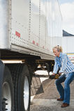 Woman Truck Driver Raising Trailer legs. Pretty blonde woman truck driver cranking the dolly handle to raise the legs of a traier after backing her tractor under Stock Images