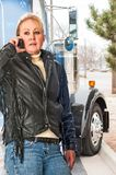 Woman truck driver talking on the cell phone to her dispatcher. Royalty Free Stock Image