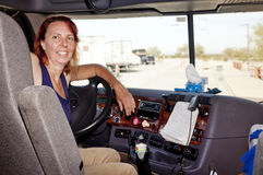 Woman Truck Driver At The Wheel. Woman driver at the wheel of her commercial 18-wheeler diesel semi truck Stock Photos