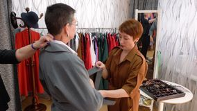 Woman Try Coat Fashion Showroom Stylists Help. Middle Aged Caucasian Woman Fit Elegant Clothes. Pretty Lady Pick up Outfit Dress Store Production Designer stock footage
