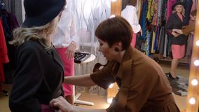 Woman Try Coat and Hat Looking at Mirror in Shop. Adult Lady Put on New Clothes in Fashion Store. Blonde Female Shopping in Boutique. Elderly Customer Dressing stock video footage