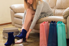 Woman try new shoes. Woman trying new shoes. young lady with long legs sitting on sofa with shopping bags on her side Stock Images