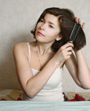 Woman  try to comb hairs Royalty Free Stock Image