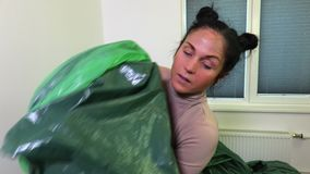 Woman try to keep green plastic bags. In room stock video