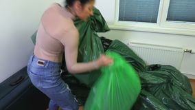 Woman try to take two plastic bags in messy room. In room stock video