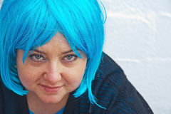 Woman trying on blue wig Royalty Free Stock Images