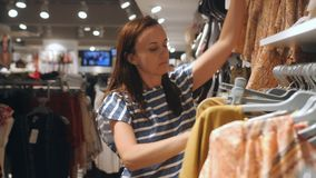 A woman walks by a clothing store and picks out new things. stock footage