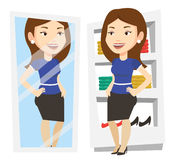 Woman trying on clothes in dressing room. Young woman looking at herself in mirror in dressing room. Girl trying on skirt in dressing room. Woman choosing Royalty Free Stock Photography