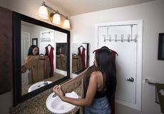 Woman Trying on clothes Looking at Mirror in Bathroom. Black female deciding between dresses and thinking about choosing a stylish fashion to wear.  She is Stock Image