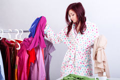 Woman trying clothes. Woman trying to decide what to wear for a date royalty free stock photo