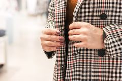Woman trying on coat in cage in the store. Focus on her hands royalty free stock image
