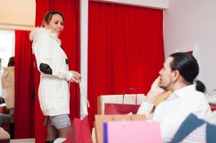Woman trying coat in fitting-room Stock Images
