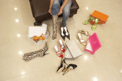 Woman trying on different pairs of high heels and boots in shoe shop, low section, elevated view Stock Image