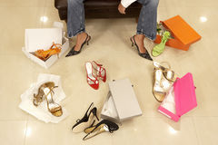 Woman trying on different pairs of high heels in shoe shop, low section, elevated view Stock Photos