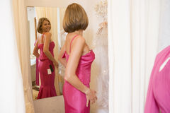 Woman trying on dresses and smiling Royalty Free Stock Photos