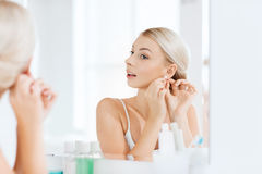 Woman trying on earring looking at bathroom mirror. Beauty, jewelry and people concept - smiling young woman trying on diamond earring and looking to mirror at royalty free stock image