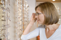 Woman trying on eyeglasses at optometrists Royalty Free Stock Photography