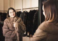 Woman trying on fur coat in women's cloths store Stock Photography