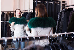 Woman trying on fur neckpiece in women's cloths store Stock Photos