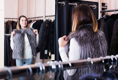 Woman trying on fur vest in women's cloths store Royalty Free Stock Photos