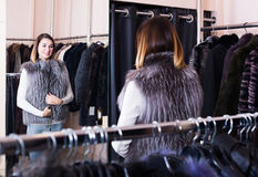 Woman trying on fur vest in women's cloths store Royalty Free Stock Images