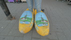 Woman trying on giant Dutch clogs in the street