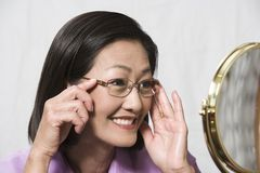 Woman Trying On Glasses And Looking At Mirror Royalty Free Stock Images