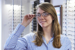 Woman Trying On Glasses In Opticians Royalty Free Stock Photos