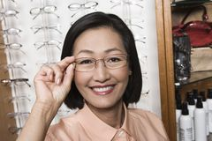 Woman Trying On Glasses At Optometrist Royalty Free Stock Images