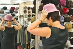 Woman trying on hat Royalty Free Stock Image