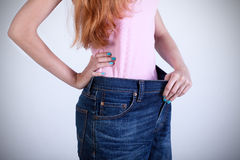 Woman trying on her old big jeans Royalty Free Stock Photos