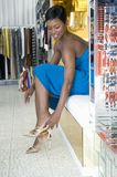 Woman Trying On High Heeled Sandals. Full length of an African American female trying on gold high heeled sandals in store Stock Photography